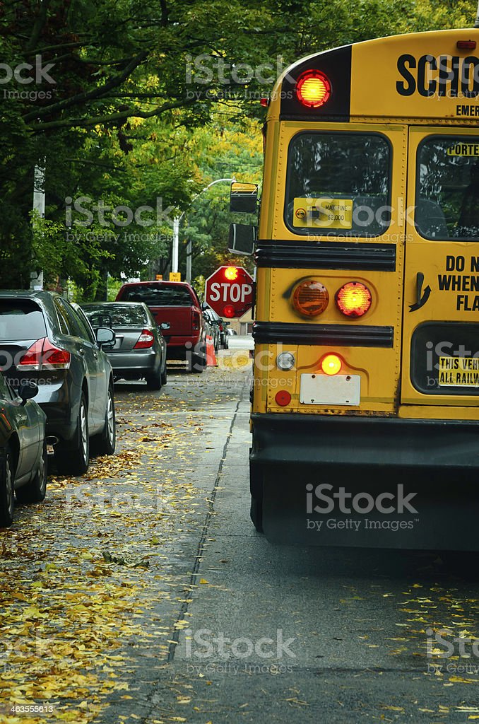 Yellow school bus with Stop sign turned on stock photo