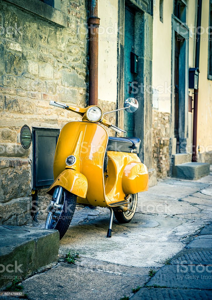 Yellow scooter in tuscan Cortona town stock photo