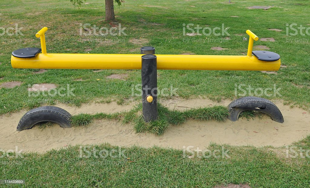 Yellow seesaw on the playground stock photo