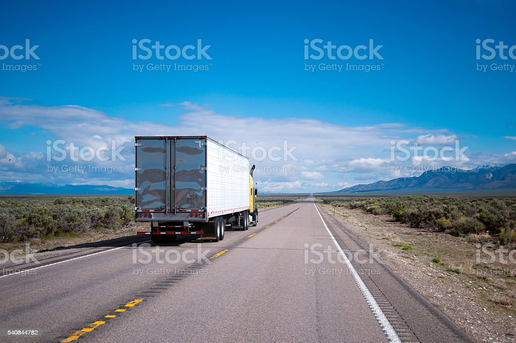 Yellow semi truck drive with commercial cargo by Nevada road stock photo