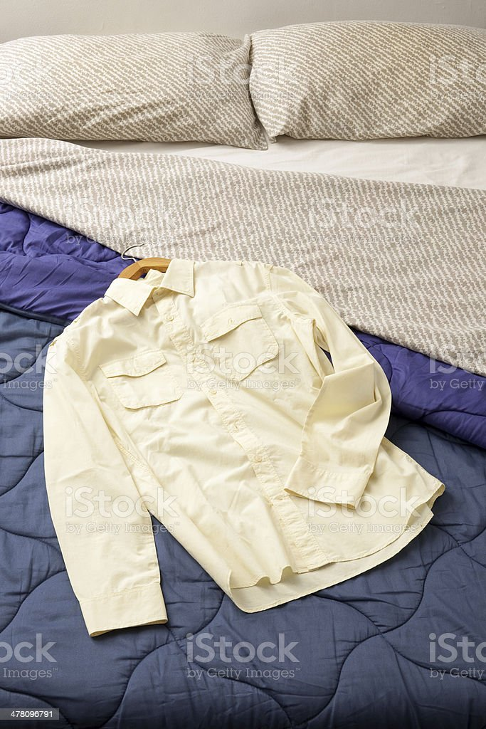 Yellow shirt over bed royalty-free stock photo