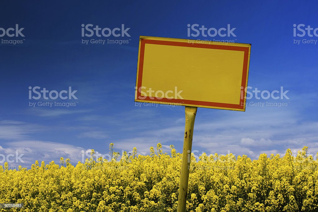 Yellow sign on rape field royalty-free stock photo