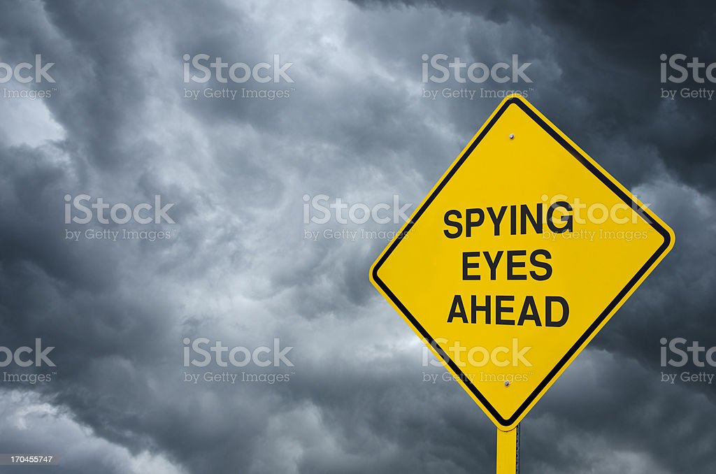 Yellow sign saying spying eyes ahead in front of dark clouds royalty-free stock photo