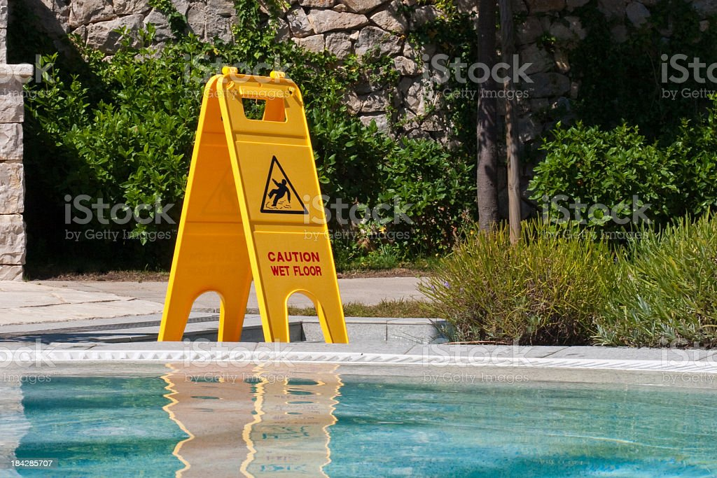A yellow 'slippery when wet' sign on the poolside stock photo