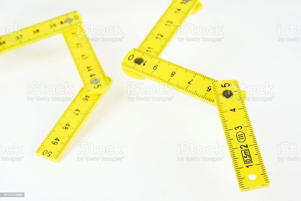 yellow small folding ruler on white background stock photo
