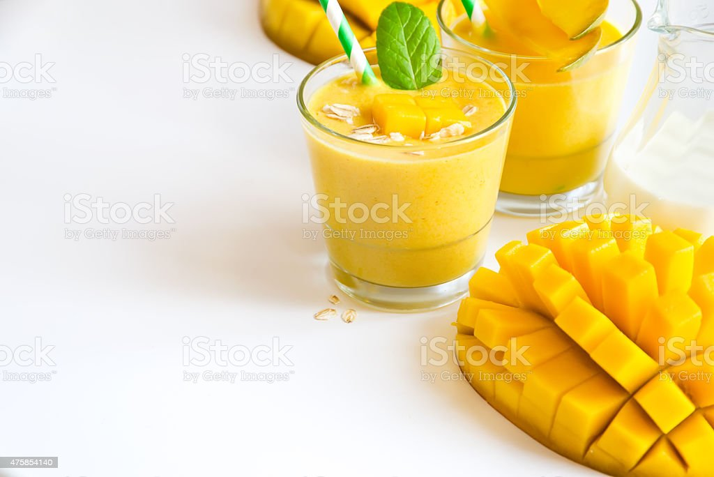 Yellow smoothie in glasses with mango white copy space backgroun stock photo