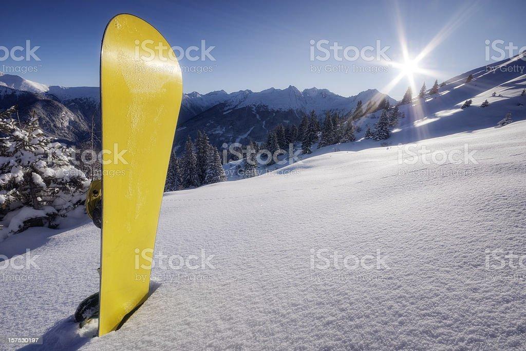 Yellow snowboard in snow on mountain stock photo