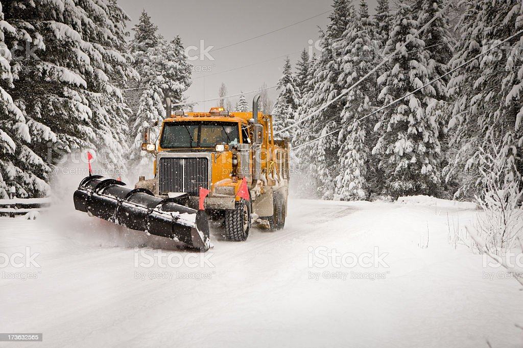 Yellow snowplow plowing through snow stock photo