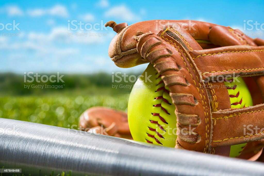 Yellow Softball in glove with aluminum bat in the grass stock photo