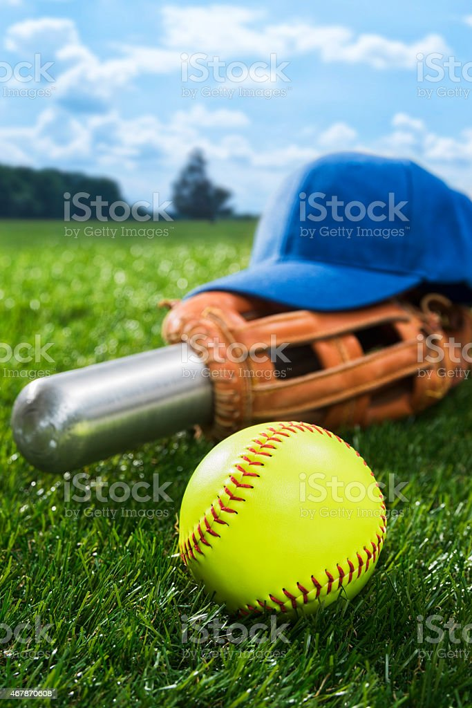 Yellow Softball in the grass with bat, glove and hat stock photo
