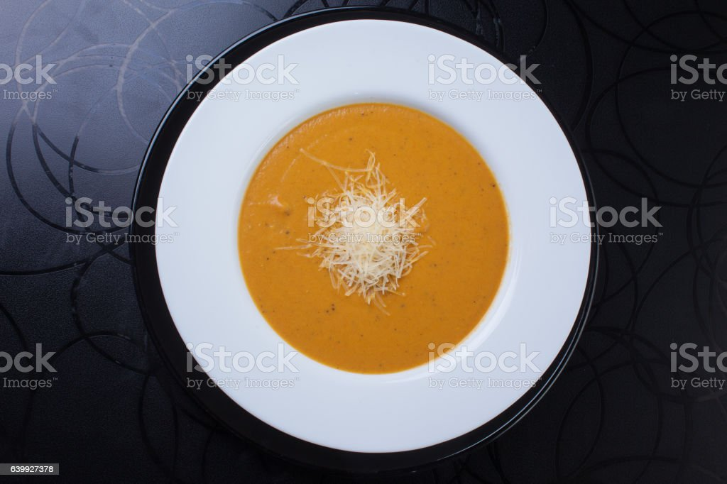 yellow soup with grated cheese stock photo