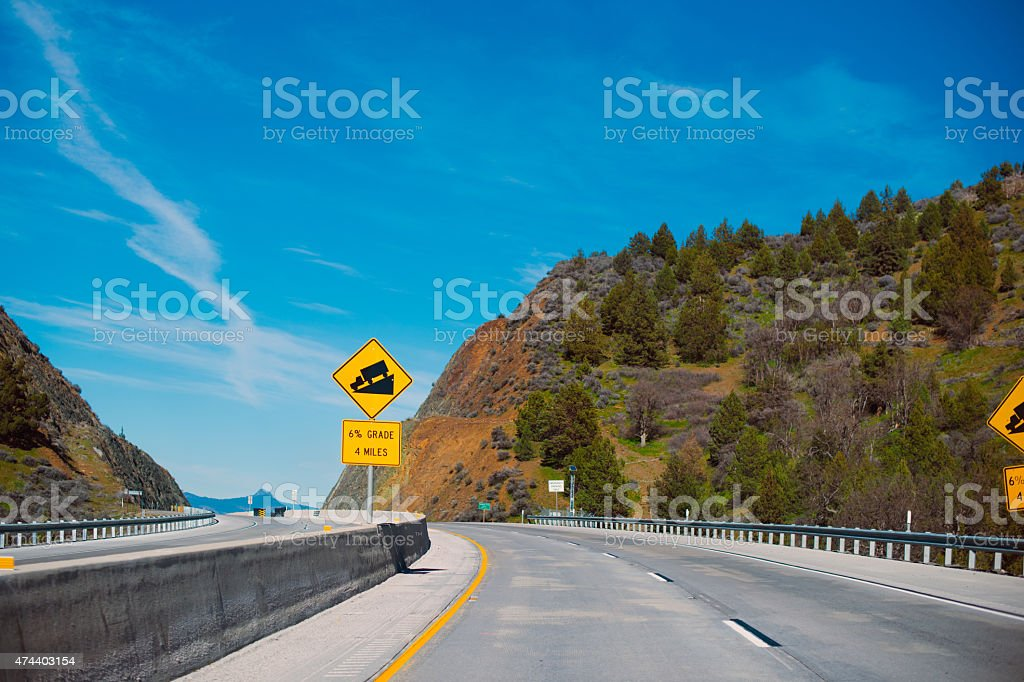 Yellow square warning information Road sign downhill pass highway Oregon stock photo