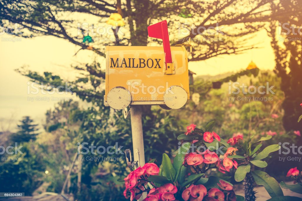Yellow stained metal mailbox has red flag raised up. stock photo