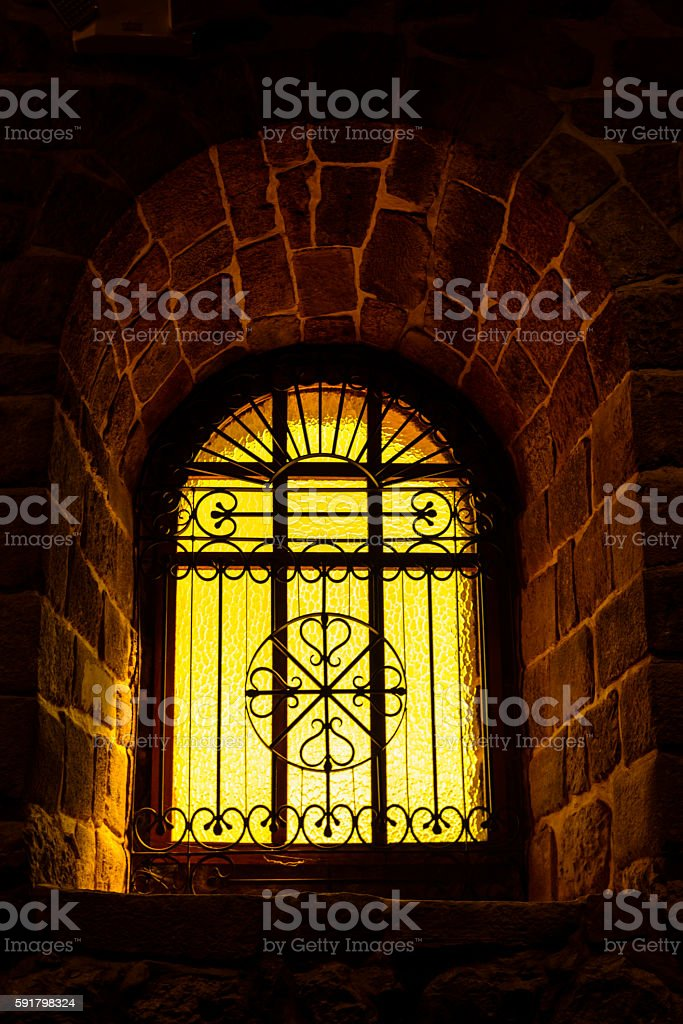 Yellow stained window with ornate wrought iron decorations. stock photo