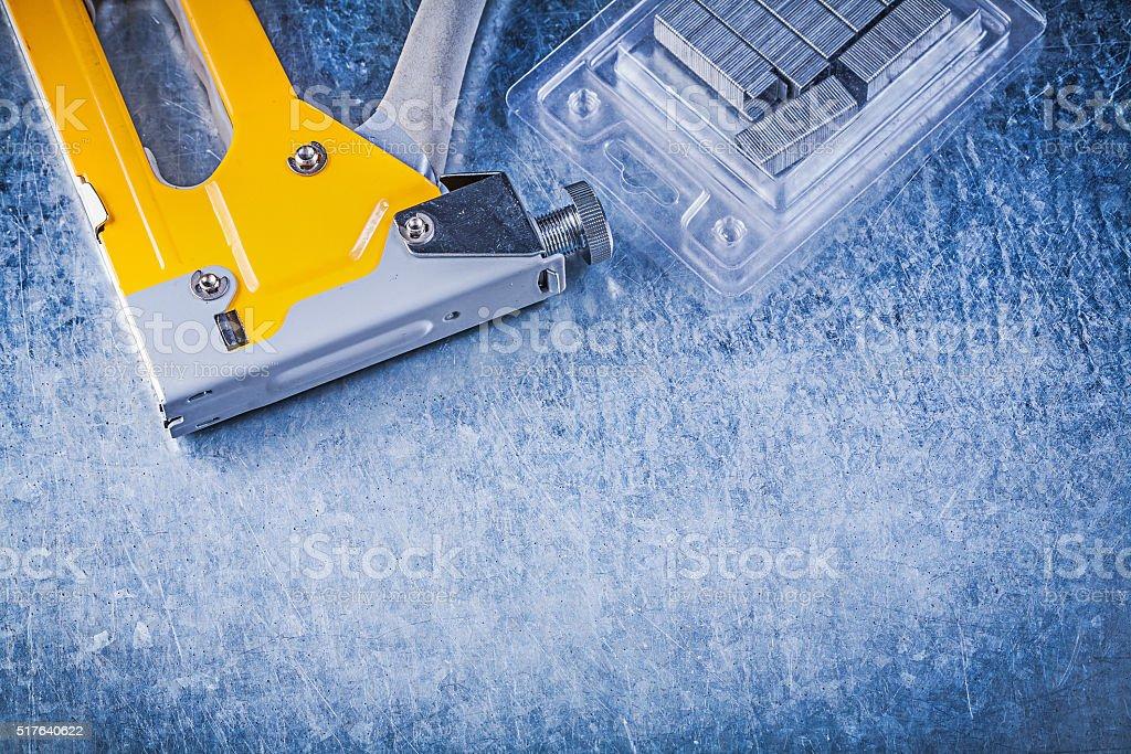 Yellow stapler gun chrome staples on scratched metallic backgrou stock photo