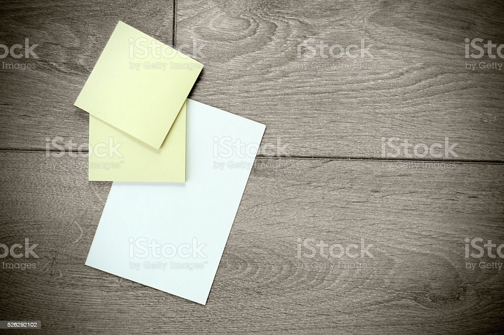 Yellow sticky papers and a white paper on wooden surface stock photo