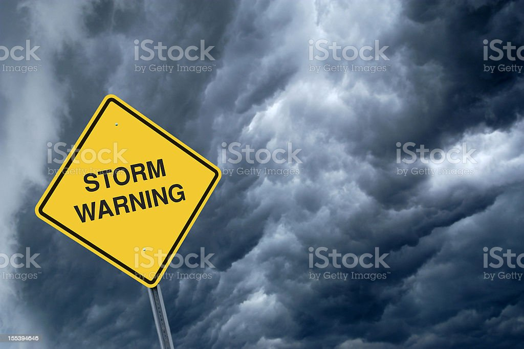 A yellow storm warning sign with storm clouds behind  stock photo