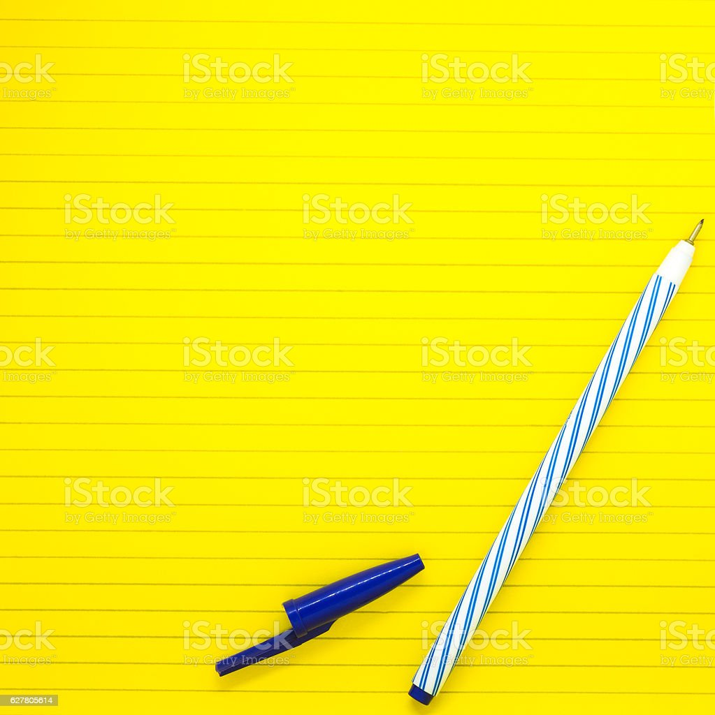 yellow study paper with blue pen ready to write stock photo