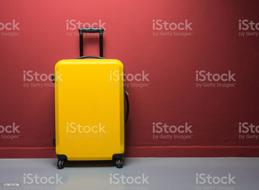 Yellow suitcase with extended handle against red wall stock photo