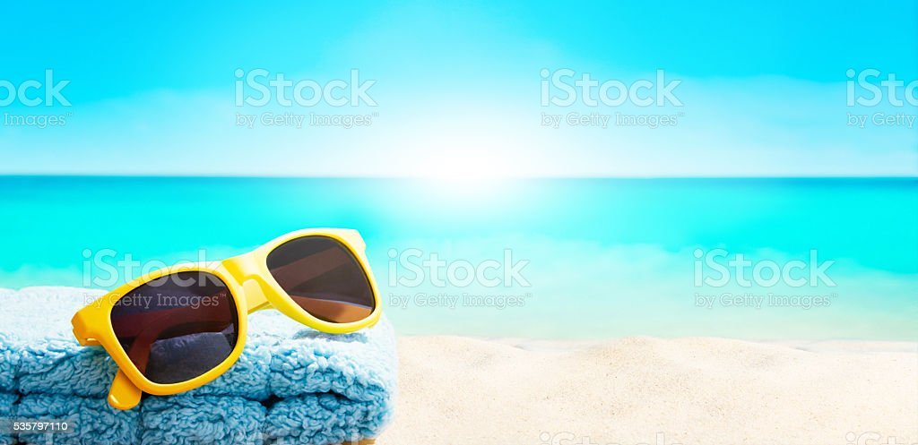 Yellow sunglasses with towel on the beach. Summer vacation image. stock photo