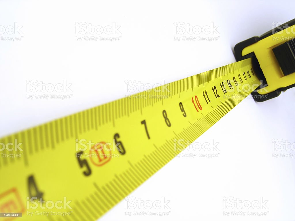 Yellow tape measure outstretched on a white wall stock photo