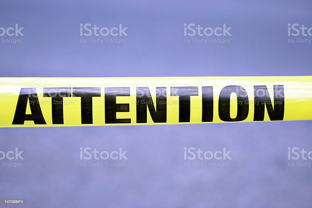 Yellow tape with word Attention stock photo