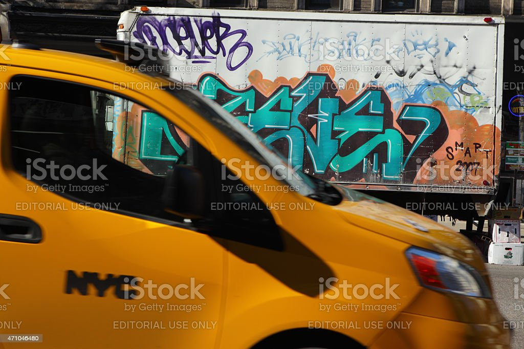 Yellow taxi cab passing a graffiti covered van in NYC stock photo