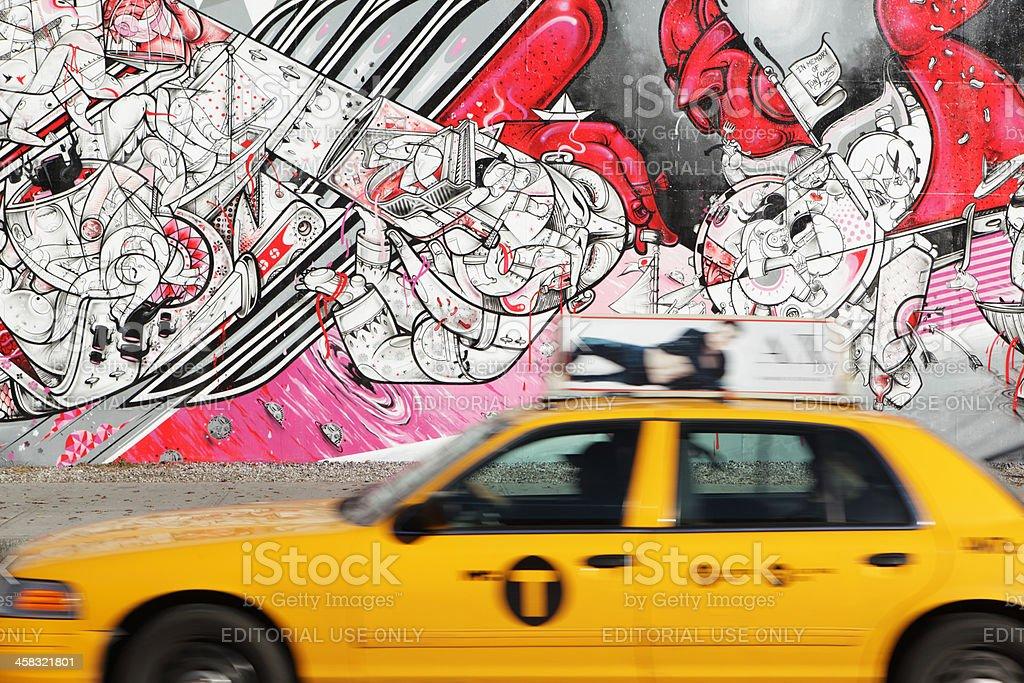 NYC yellow taxi speeds past How Nosm street art mural stock photo