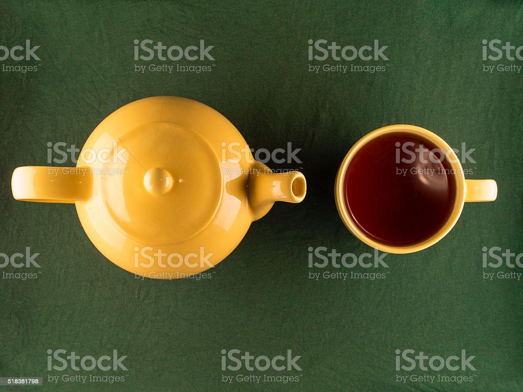 Yellow teapot and mug with tea, copy space stock photo