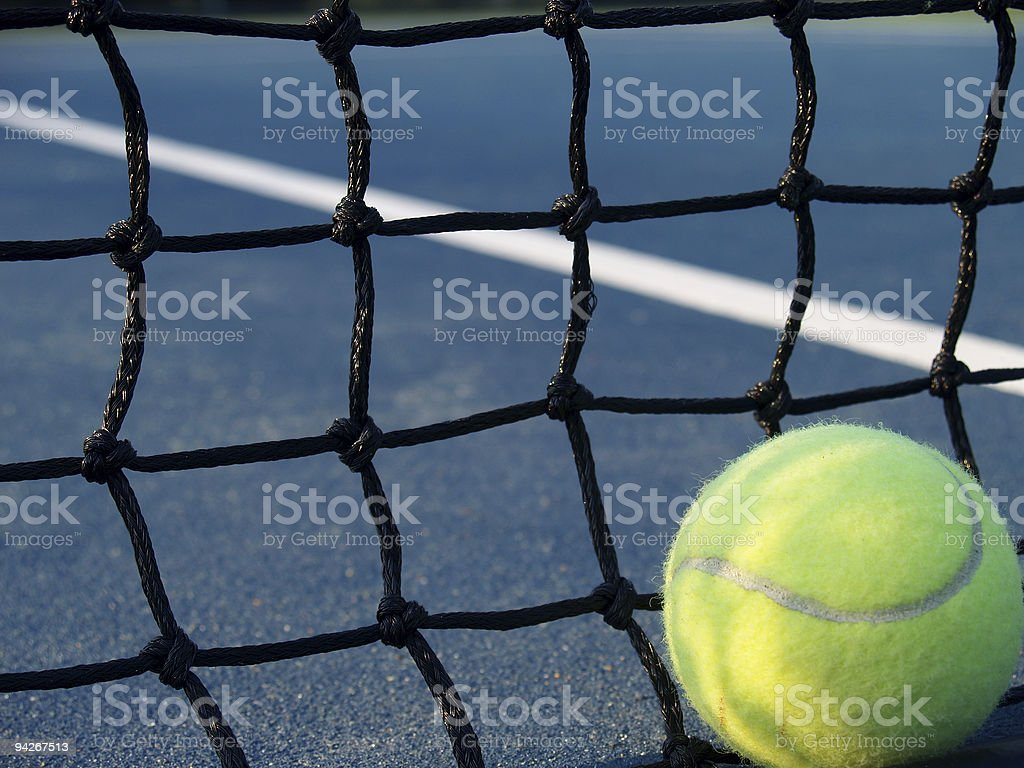 A yellow tennis ball and a black net stock photo