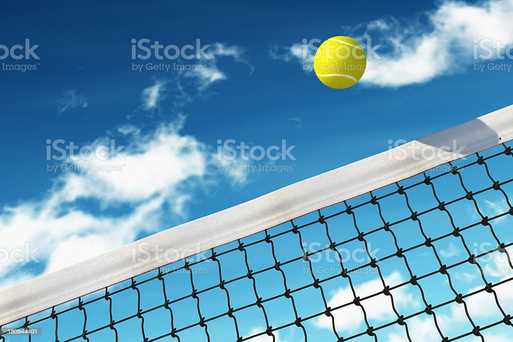 A yellow tennis ball flying over the net royalty-free stock photo