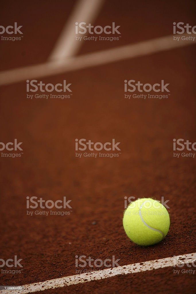 yellow tennis ball on a clay court royalty-free stock photo