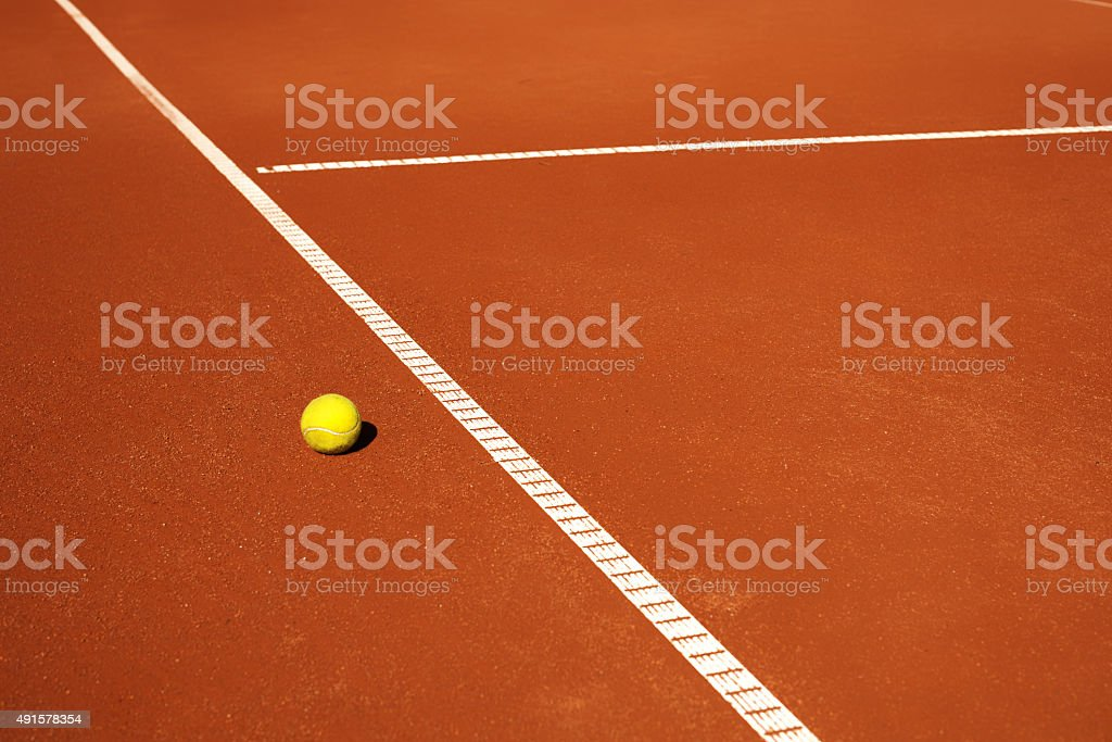 yellow tennis ball on a red clay court stock photo