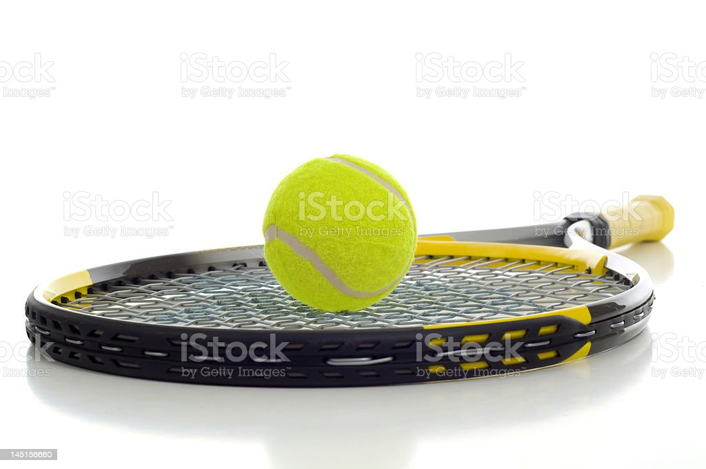 Yellow tennis ball resting on a tennis racket royalty-free stock photo
