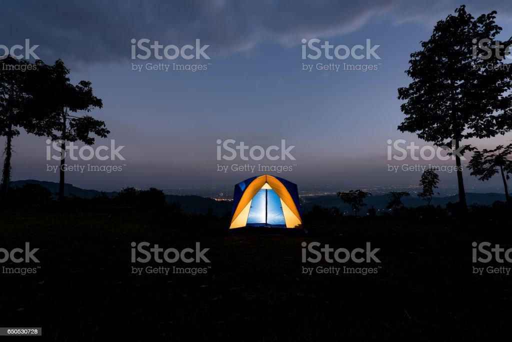 Yellow tent illuminated at dusk on summer mountain ridge stock photo