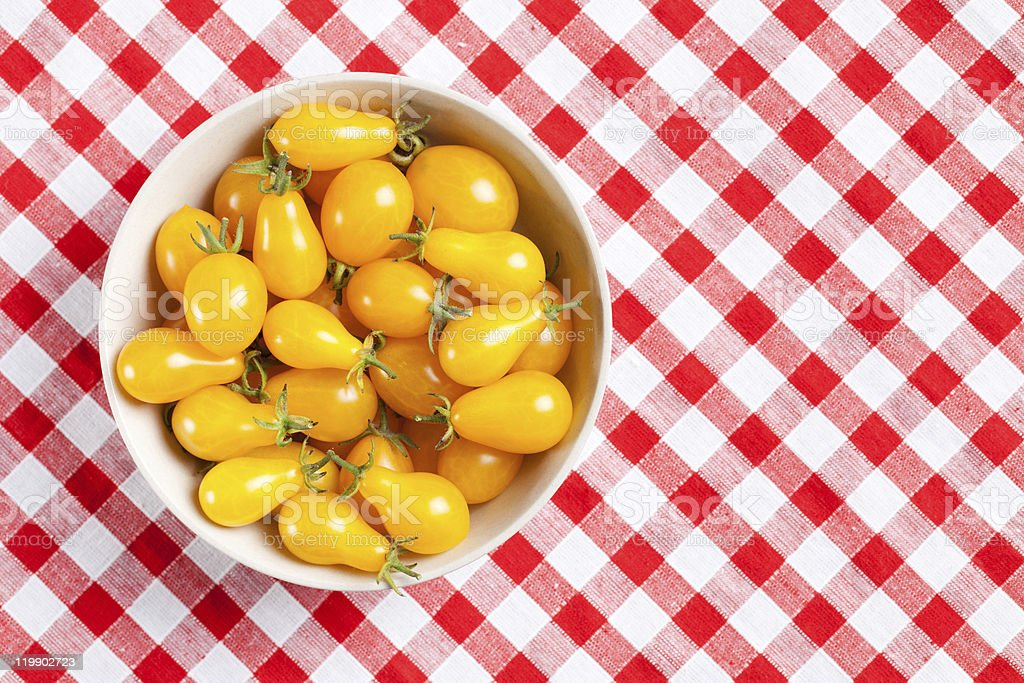 yellow tomatoes on picnic tablecloth stock photo