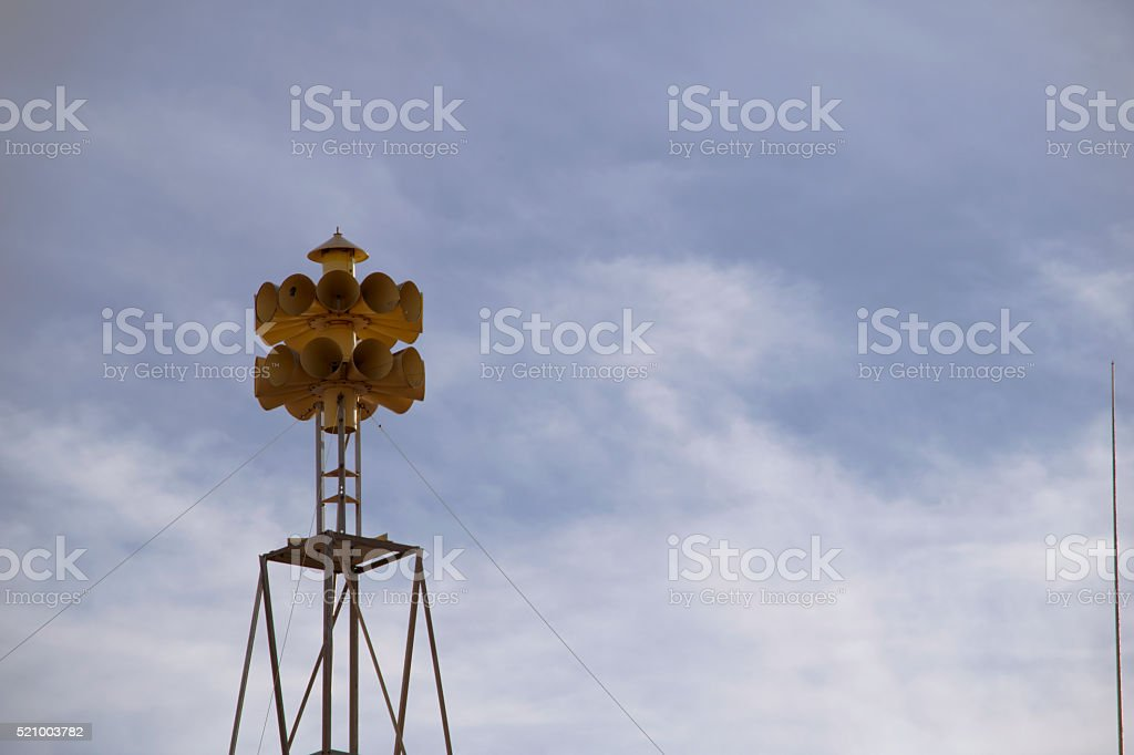 Yellow tornado siren in a sunny sky stock photo