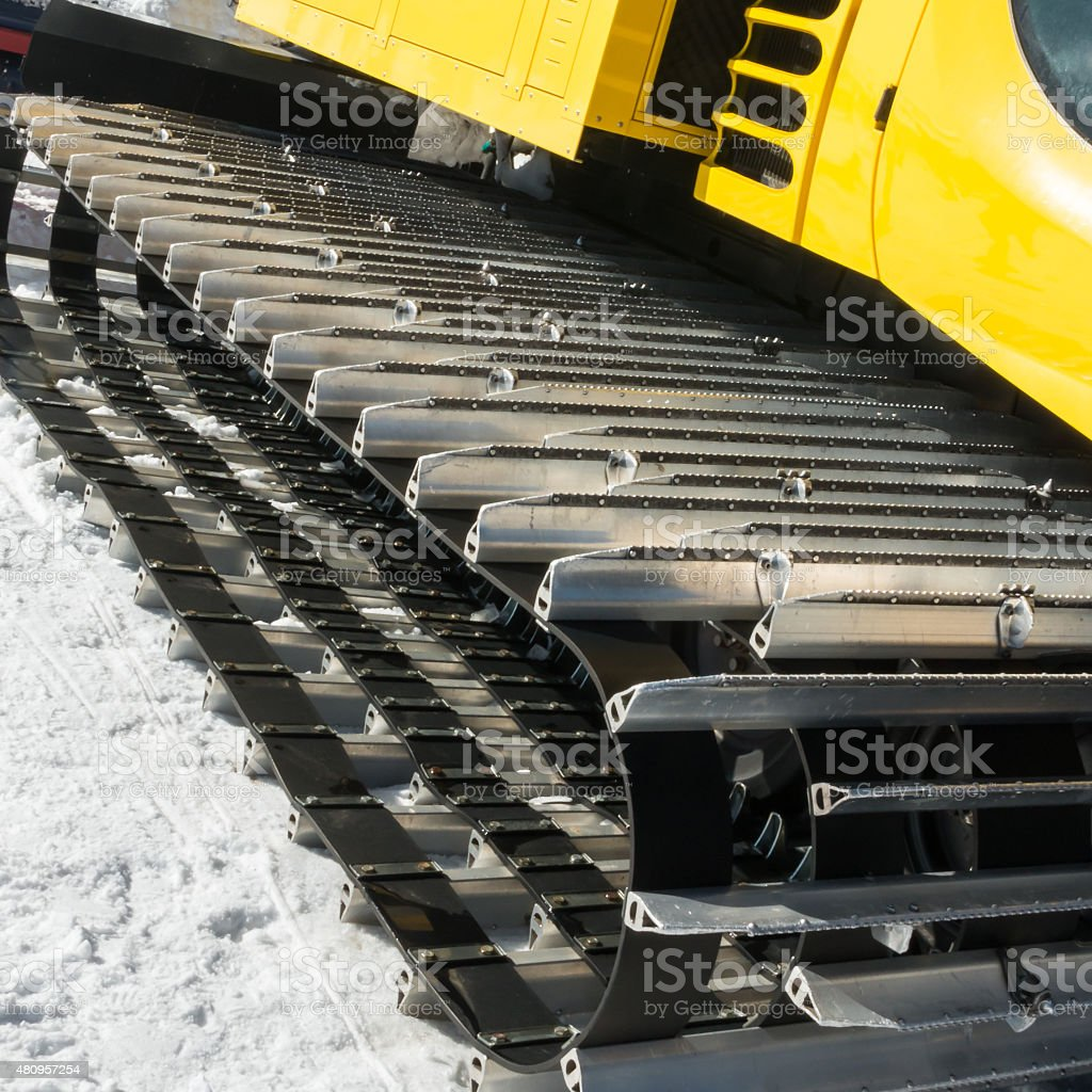yellow tracked vehicle on snow, grooming machine stock photo