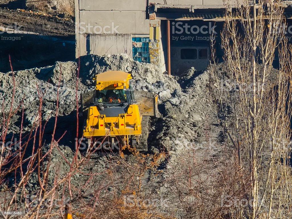 Yellow tractor rakes buckets clay near the plant closeup stock photo