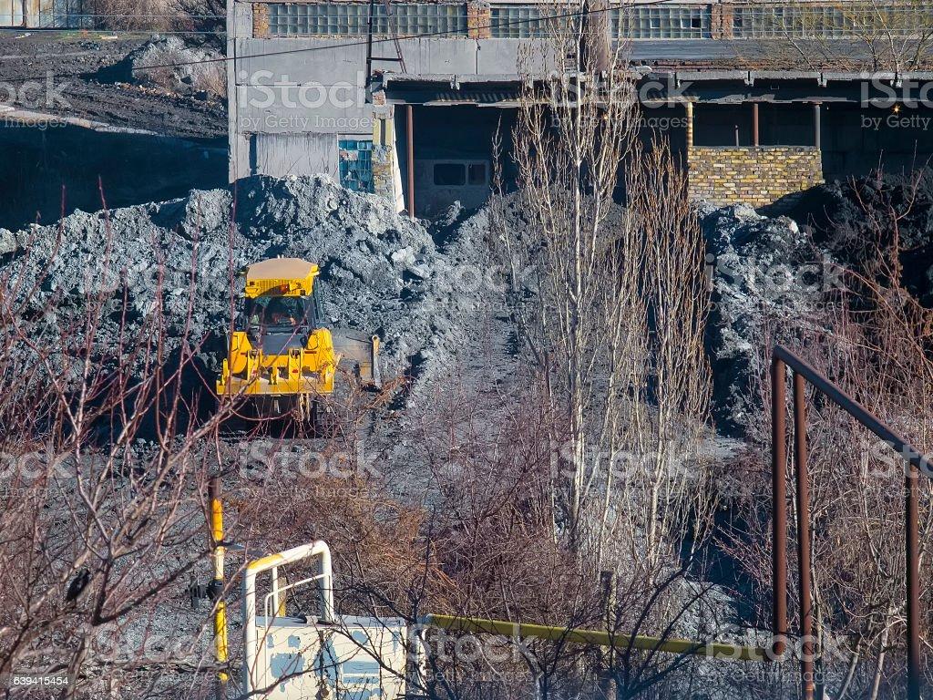 Yellow tractor rakes buckets clay near the plant stock photo