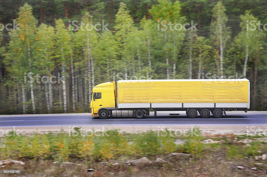 yellow trailer goes on highway royalty-free stock photo