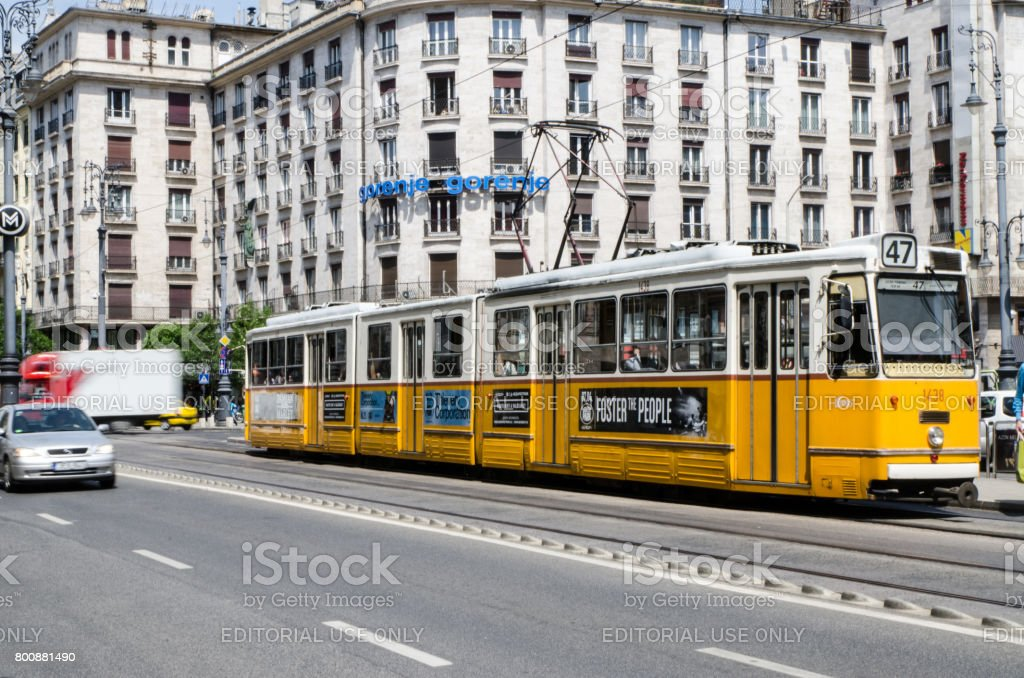 Yellow tramway and cars passing by on street in Budapest during summer day stock photo