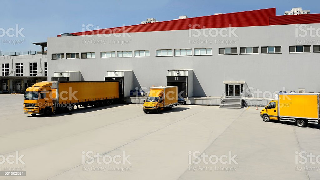 Yellow Transport Truck Docking in Warehouse stock photo