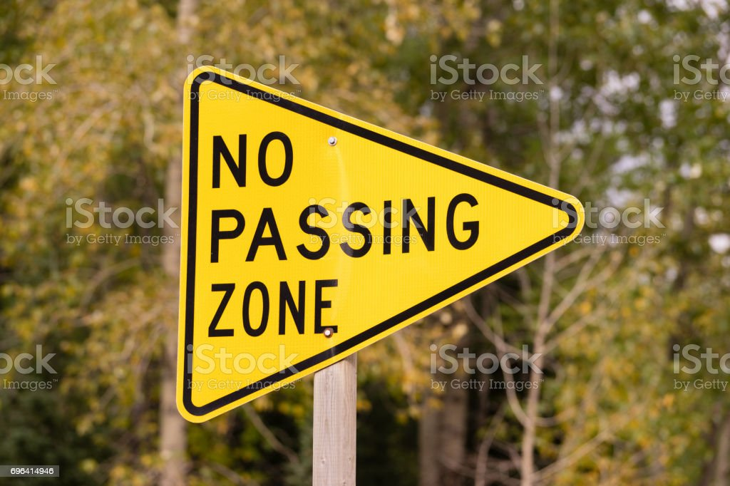 Yellow Triangle Road Sign Warning No Passing Zone stock photo