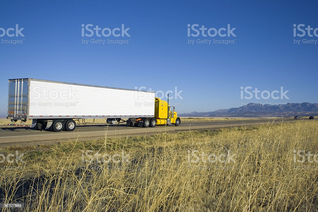 Yellow truck driving towards mountains. stock photo