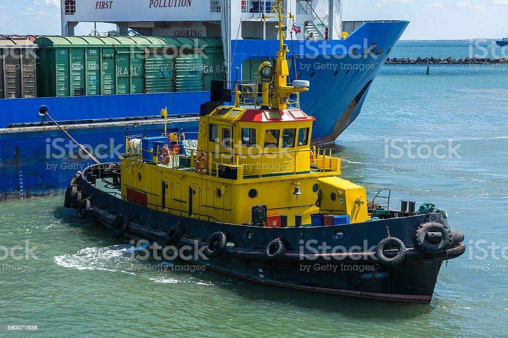 Yellow tugboat assisting large cargo ship stock photo