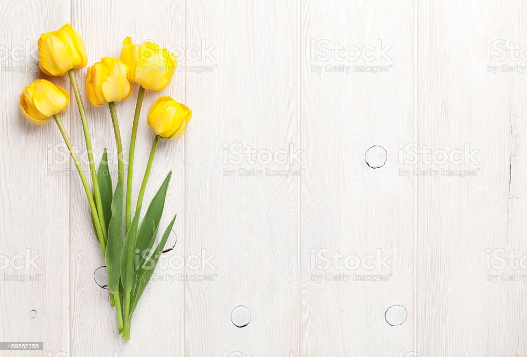 Yellow tulips over wooden table stock photo