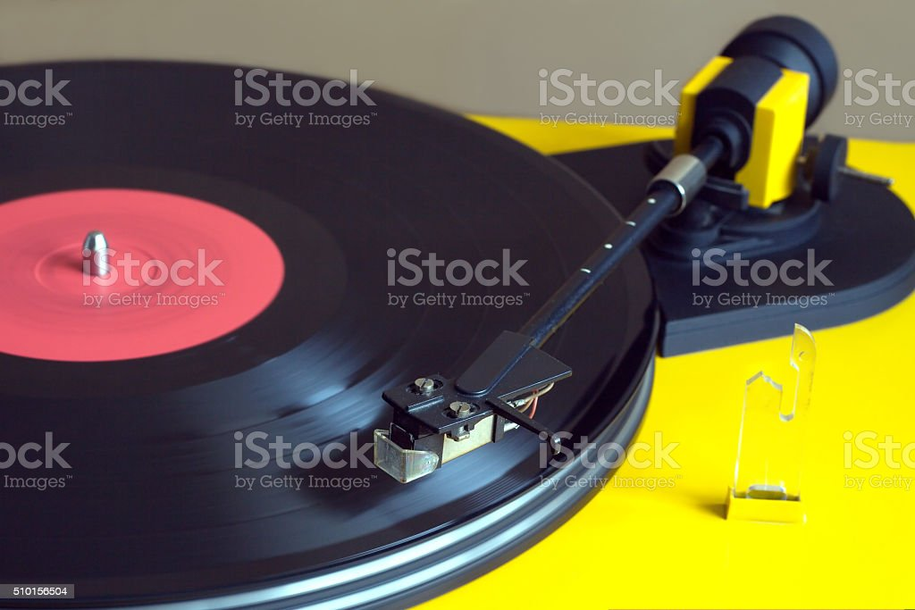 Yellow turntable with vinyl record closeup stock photo