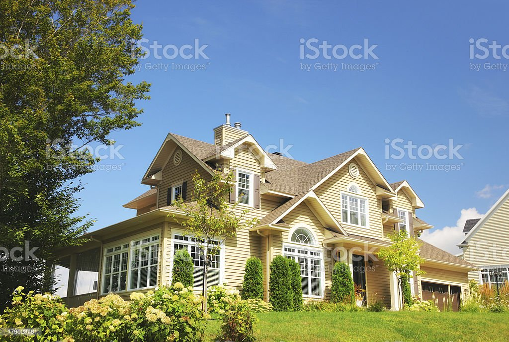 Yellow two story country house on summer day stock photo