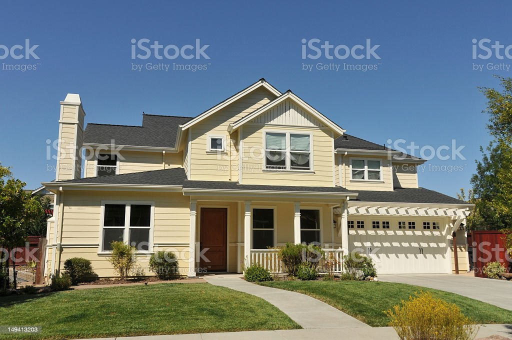 Yellow two story house with garage and driveway and fence stock photo